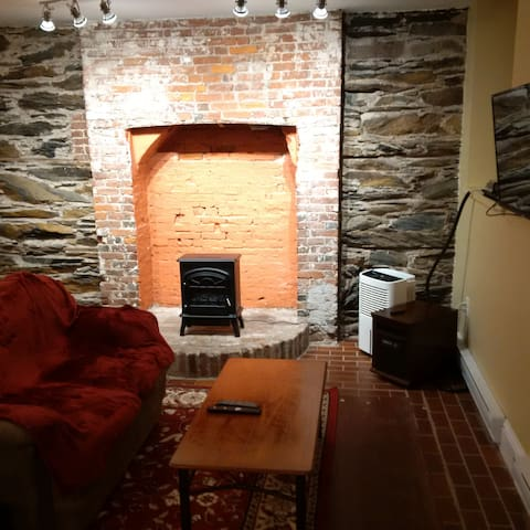 """The rock wall and brick hearth add character and """"chic"""" to this apartment. The little """"woodstove"""" is an electric heater that provides extra warmth on cold nights."""