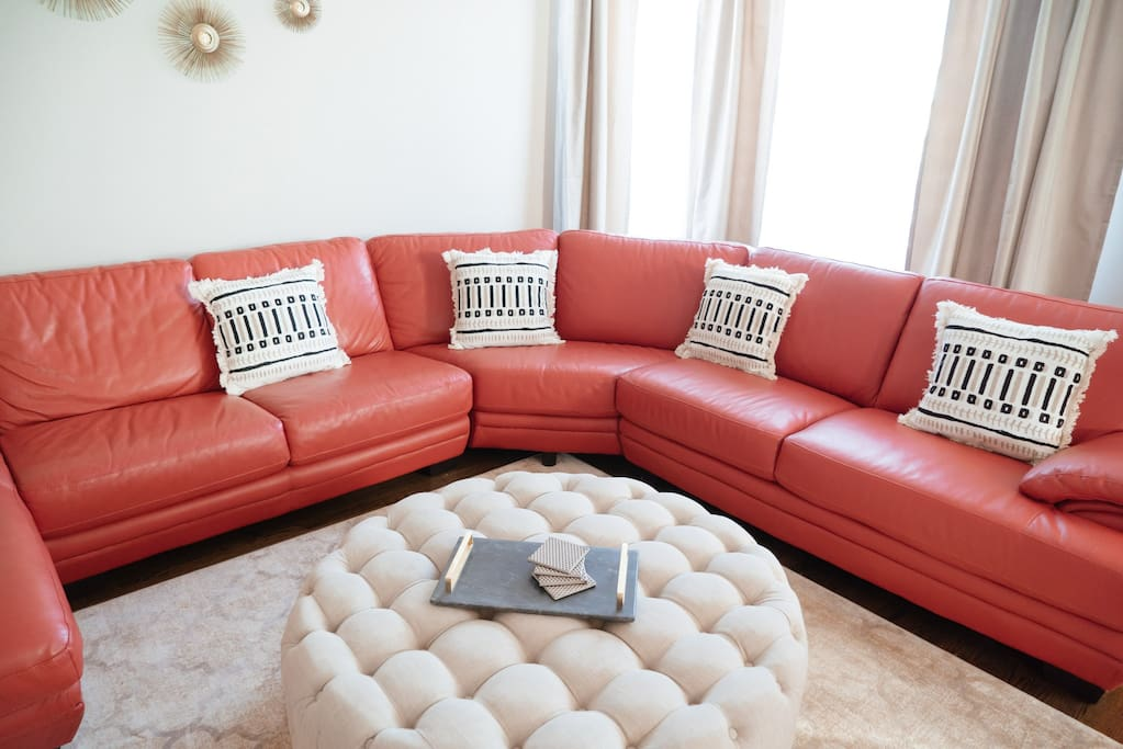 High-end furnishings include a leather sofa, throw pillows, and ottoman