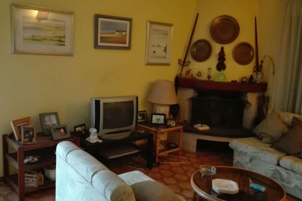 Sala de estar com TV, lareira e 3  sofás, sendo 2 sofás- cama, muito confortável