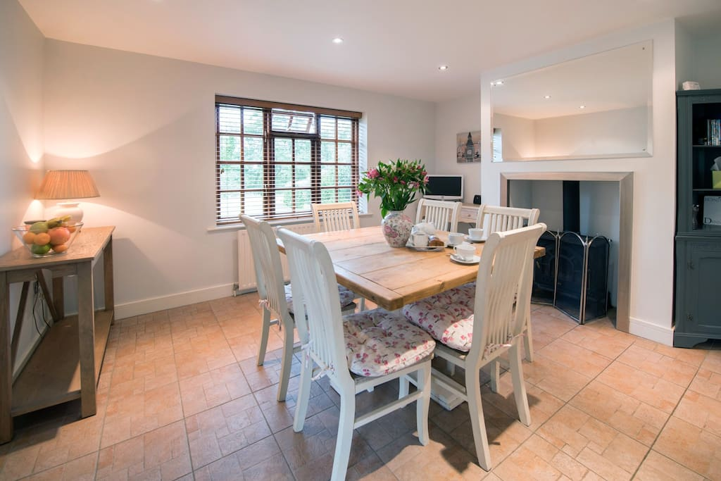 Log burner, dining table for 6 guests and kitchen area with separate breakfast bar for two.