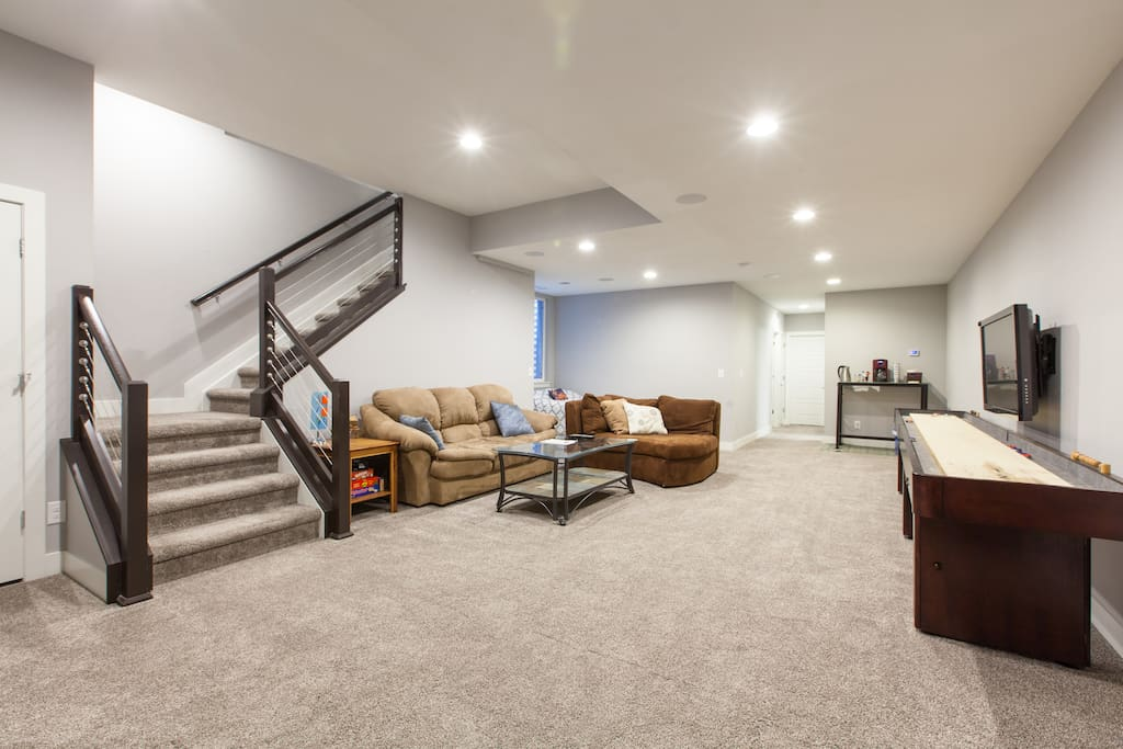 Spacious and private basement living room with shuffleboard table, TV, games and more.