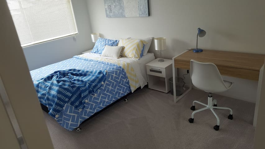 Blue room with large mirrored wardrobe and office desk & chair. Zoned Ducted aircon.