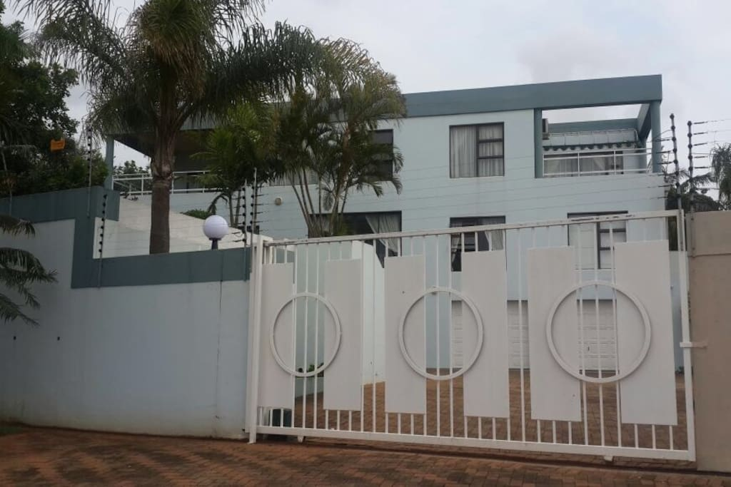 The outside look of the house showing all three storeys, remote controlled gate and electric fence. The house is in a safe neighbourhood with Blue Security 24/7 response unit and street foot patrol stationed by our gate.