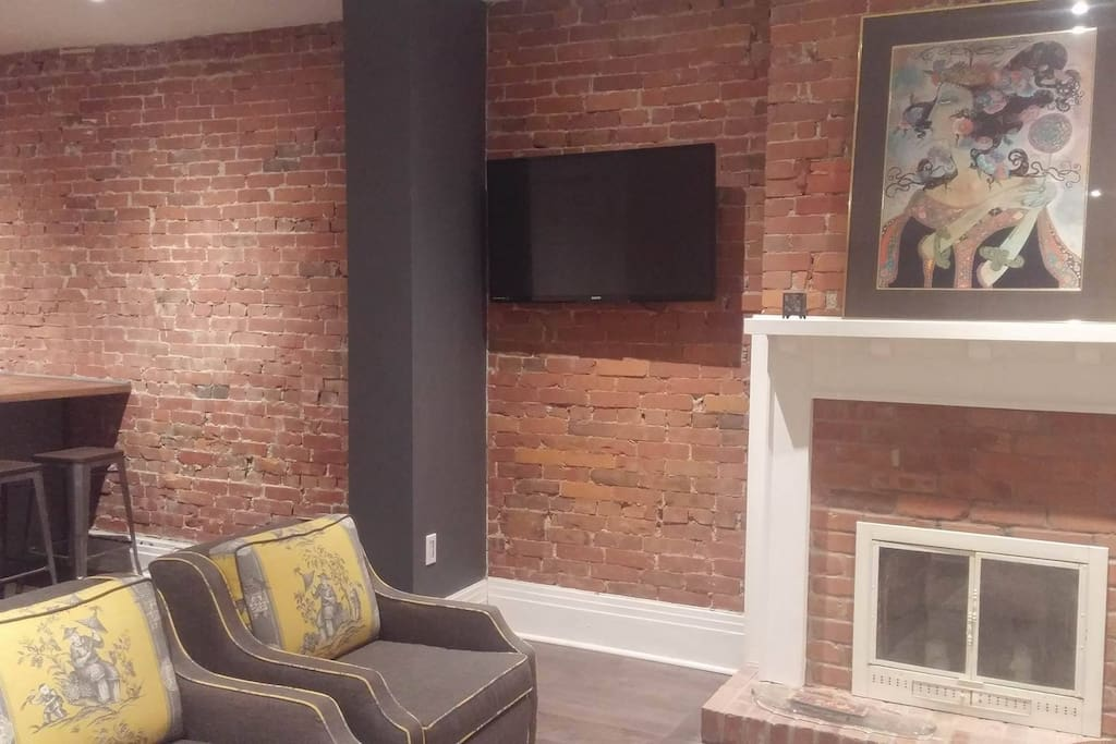 exposed brick, artwork and new flat screen television mounted on bracket.