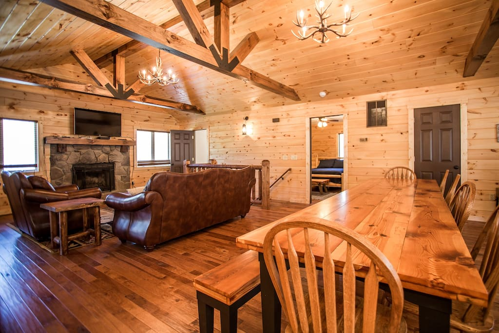 Beautiful rustic lodge home with leather sofas, flat screen TV, wood burning fireplace, and antler chandeliers.
