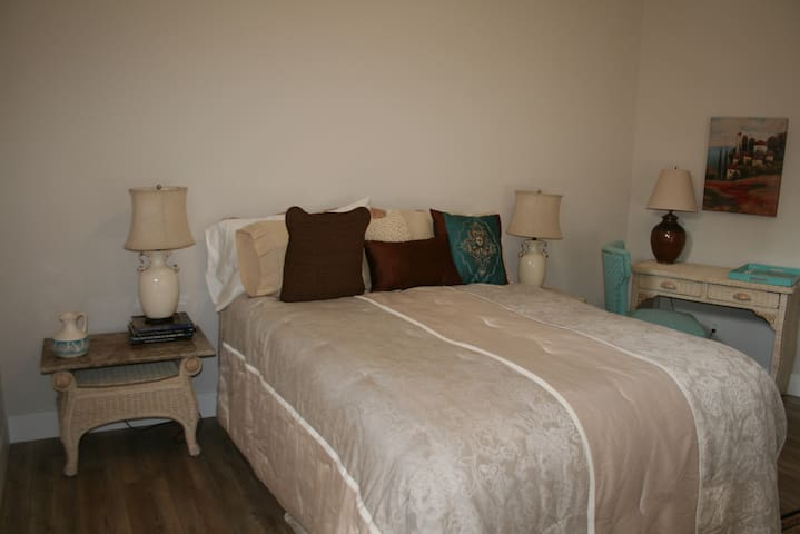 """Master bedroom, the """"Turquoise Room"""" with queen sized bed, desk, dresser, and French doors to courtyard."""