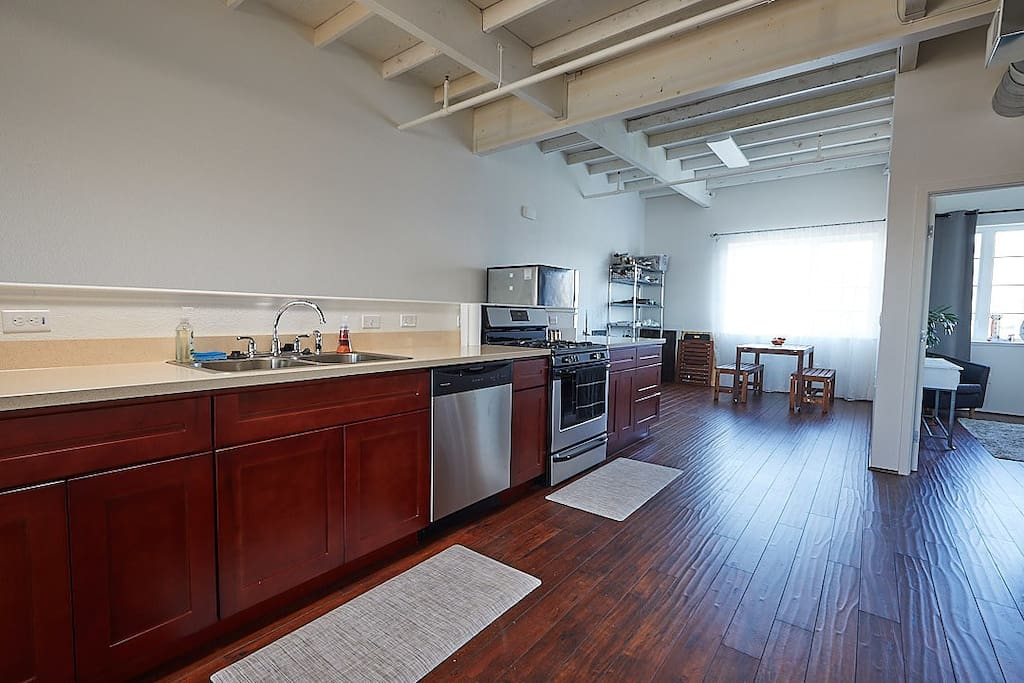 Spacious kitchen with anti-fatigue mats, electric water kettle, coffee maker, toaster, dishwasher, fridge/freezer, gas range, slow cooker, dish drying rack, and all the basics for cooking and dining.