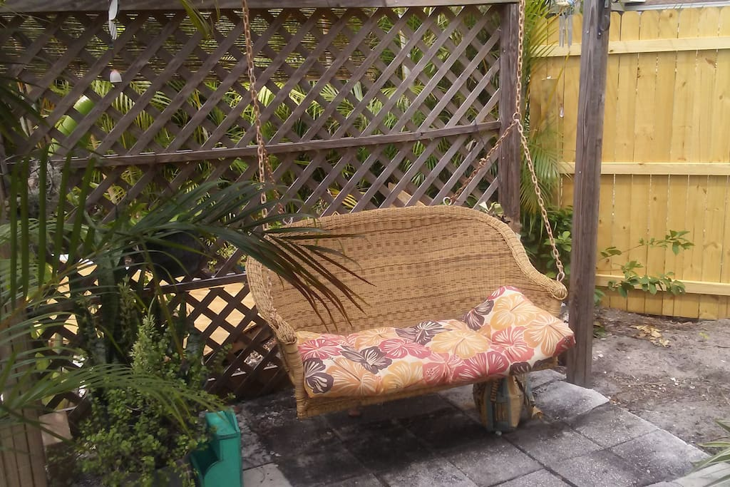 a swing love seat by fish pond
