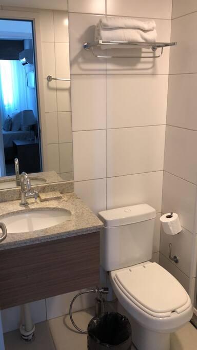 Banheiro com toalhas e papel higiênico
