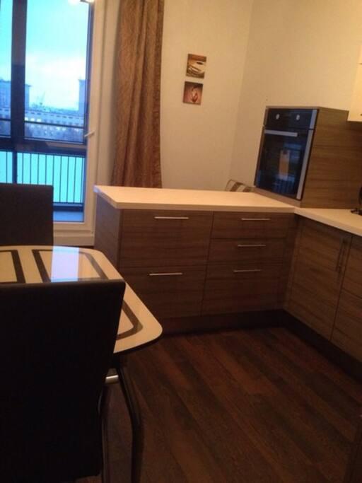 Современная кухня с обеденным столом и удобным диваном для гостей
