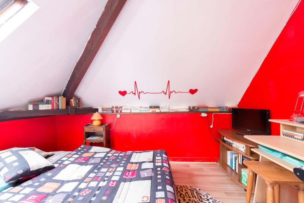 la même chambre rouge avec sa télé et son bureau