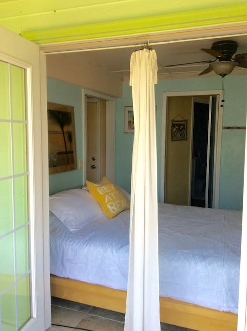Queen bedroom opens to outdoor sitting area and tropical landscaping.