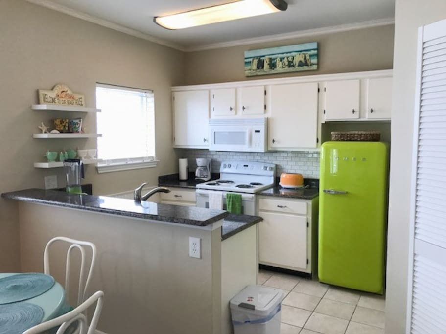A vintage-inspired green fridge adds color in the fully stocked kitchen.