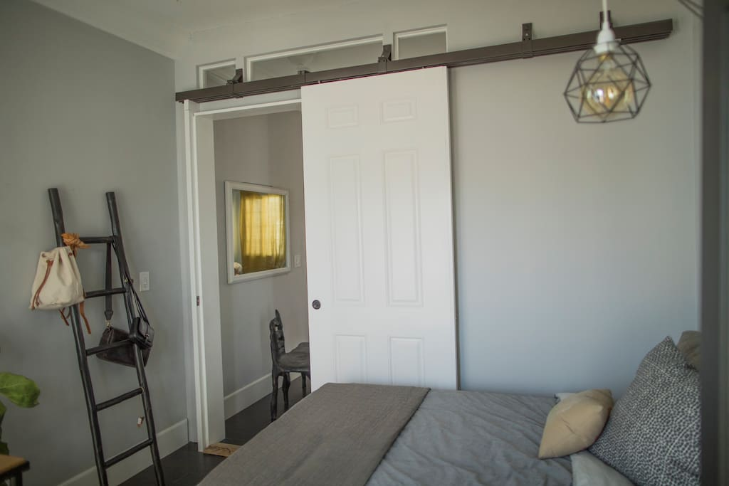 Guest room with barn door opening into shared space