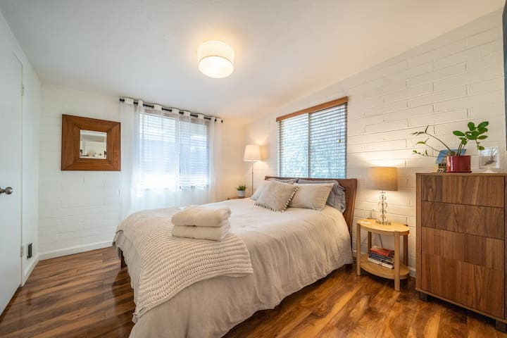 Master bedroom. A comfortable queen bed with high-quality cotton and linen bedding with lots of pillows.  The bedroom has a large closet, a dresser and bedside tables on each side.