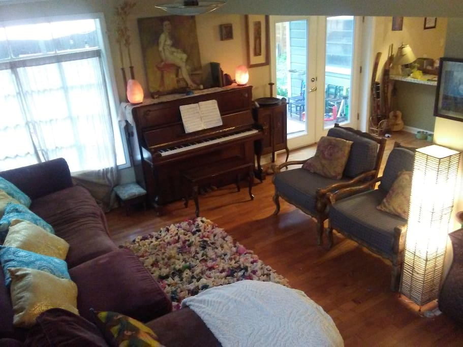Living area with sectional sofa and chaise lounge as well as piano guitar and didgeridoos