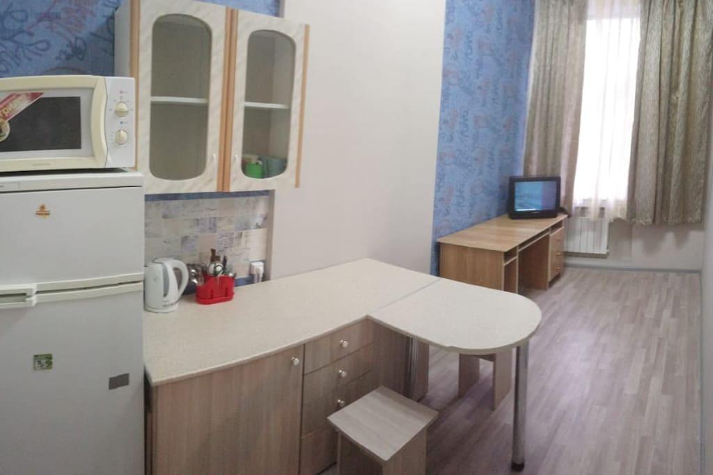Первая комната оборудована как кухня (холодильник,электрический чайник,микроволновка, небольшой стол для двух или трех человек,так же имеются ложки, вилки,ножи,досточка, сковородка,кострюли,кружки,вилки).Так же имеется 3 табуретки,компьютерный стол и телевизор.Новый ремонт,дорогие обои,линолеум, натяжной потолок,люстра,металл пластиковые окна.
