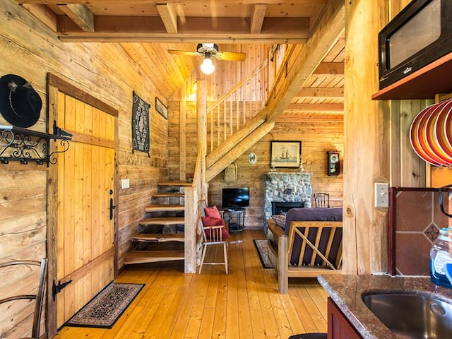 Enter the cabin into an open concept kitchen, dining area and living room with fireplace