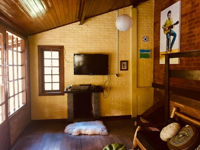 Sala com tv, lareira e varanda.