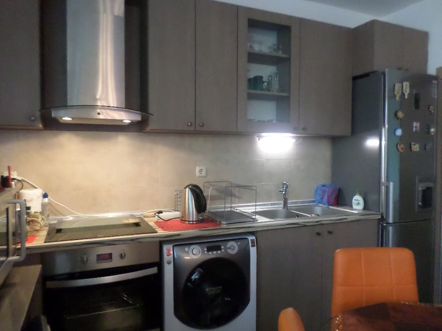 Kitchen with double basin, extractor above ceramic top, oven, large fridge/ frizzer and water dispenser, microwave, toaster