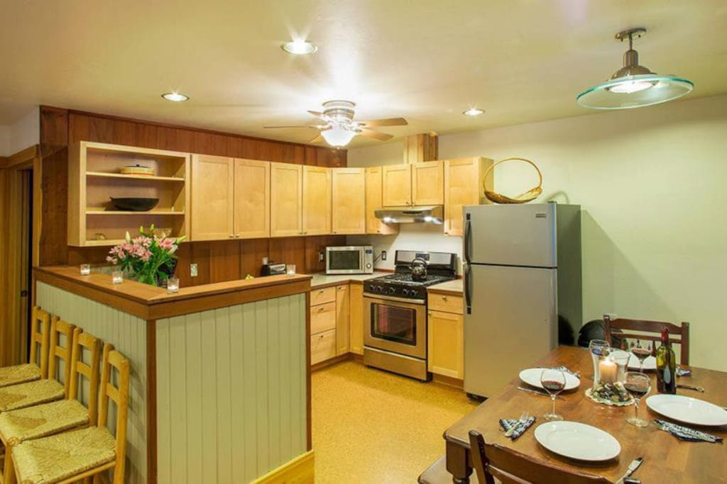 Fully equipped kitchen with all dishes, pans, coffee maker, open to living room
