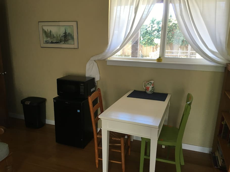Eating area with a mini fridge, microwave, coffee maker, hot water kettle, dishes, and silverware.