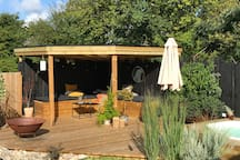 Pergola with covered roof, facing the pool and the house.