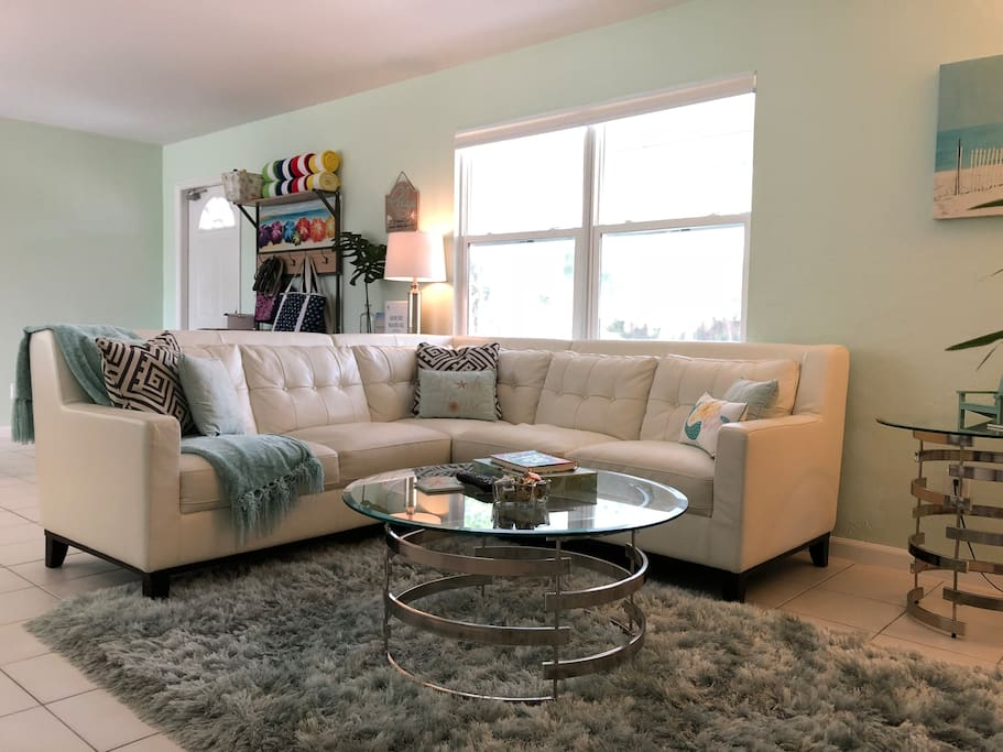 """Living room with white leather sectional, plush shag rug, and 50"""" HD TV."""