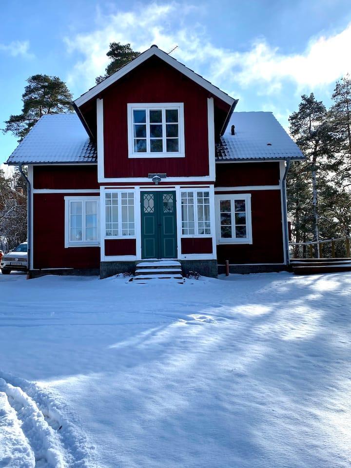 Nyrenoverat sekelskifteshus med utsikt över sjö.