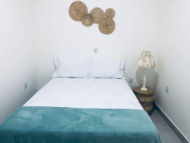 Quarto com cama de casal, aparador ao lado da cama e decoração em palha!