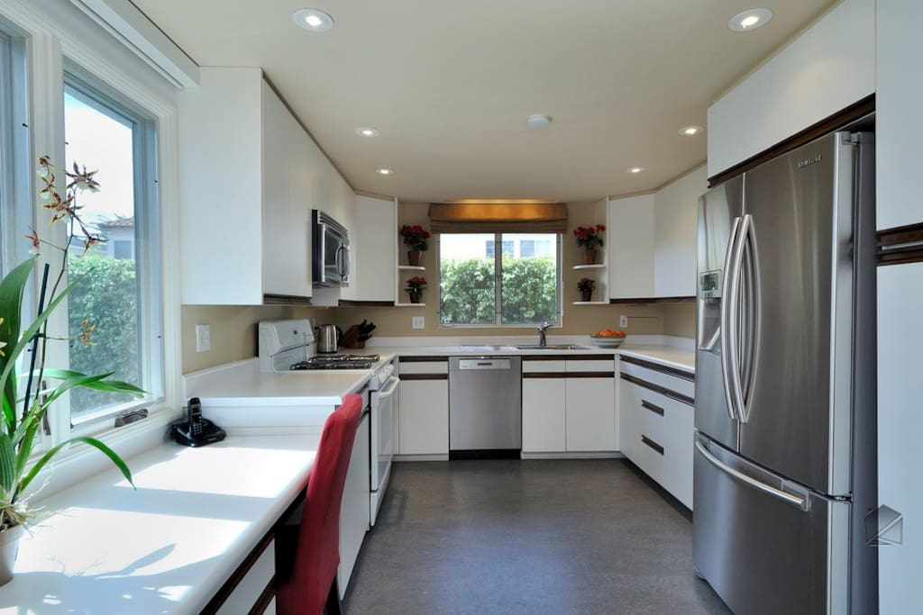 The sleek, modern kitchen has a Samsung stainless steel refrigerator, Miele dishwasher, microwave, built-in desk, and gas stove and oven.