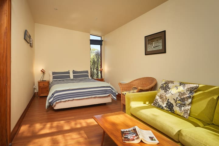 Queen bed in second room, dual purpose room with TV and sofa. This room has large window looking onto the garden