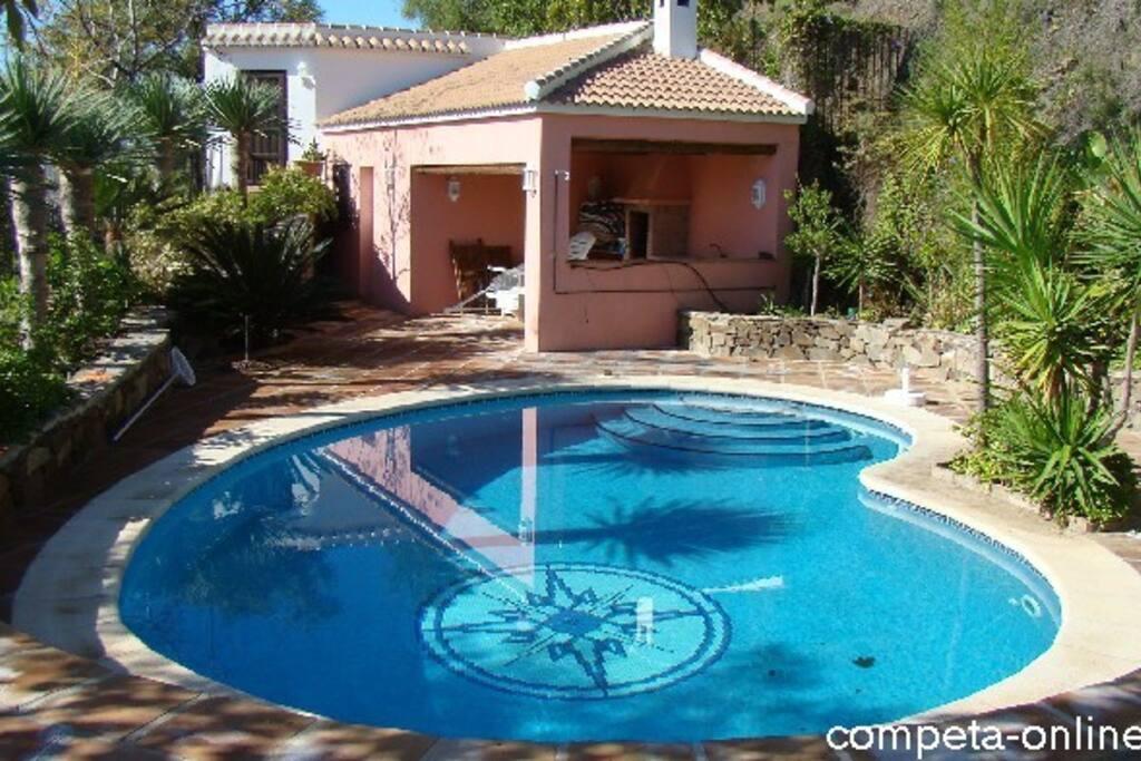 Blick über den Pool auf das Gästehäuschen und den überdachten Grillbereich