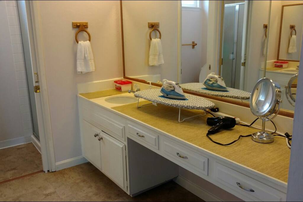 Vanity area with sink, hairdryer, lighted mirror, iron, and ironing board.