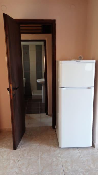 Fridge and door leading to bathroom and bedroom