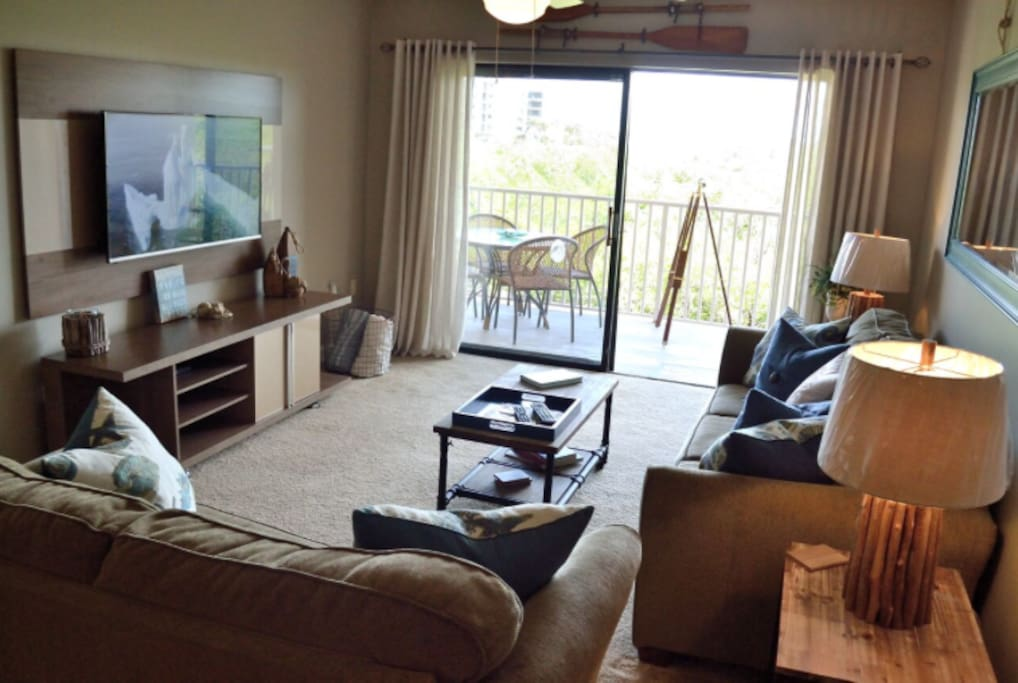 Our comfy living room offers a new large flat screen TV,  sleeper sofa and access to our balcony.