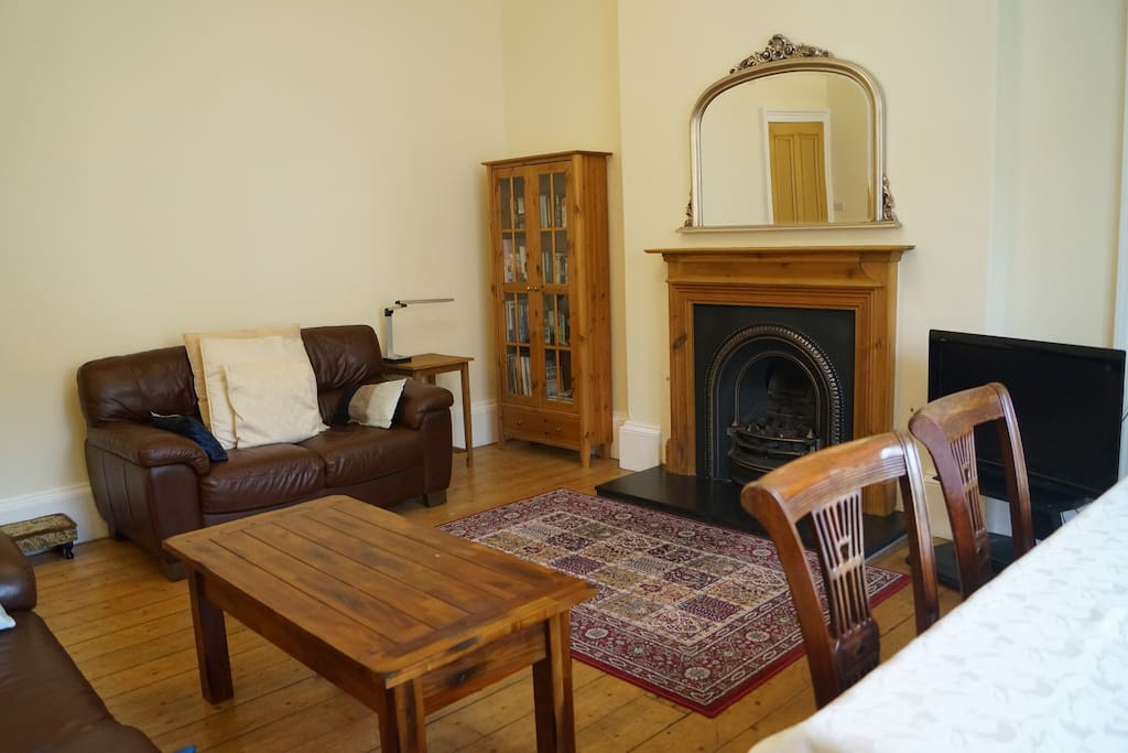 Living room with view to private garden belonging to flat. 2 sofas, TV, DVD player, gas fireplace, dining table, period features.
