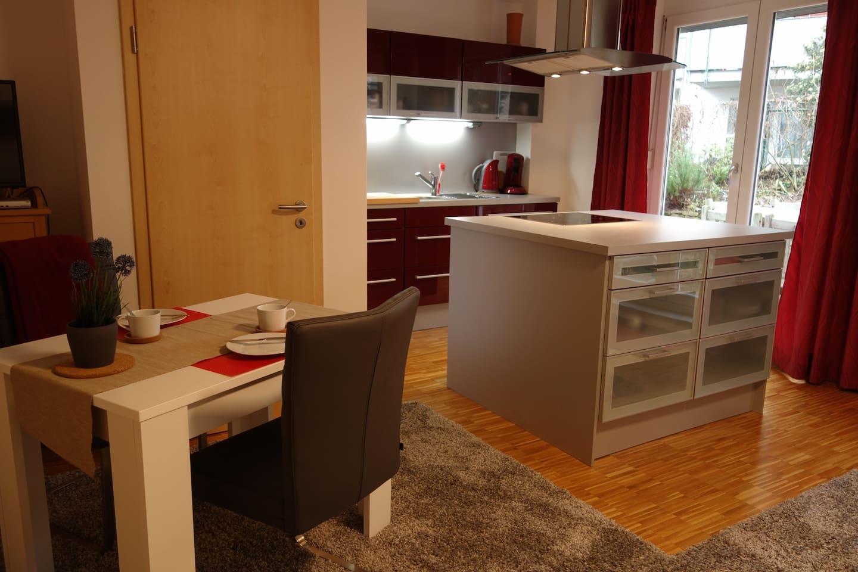 Küche mit Kochinsel, kleiner Esstisch (Die Tür zum Treppenhaus ist verschlossen) Bett 140x200 ist im gleichen Raum