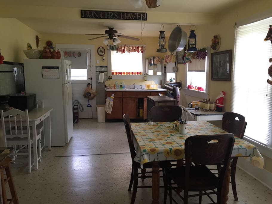 Farmhouse kitchen with refrigerator, stove, sink, table seating for four.