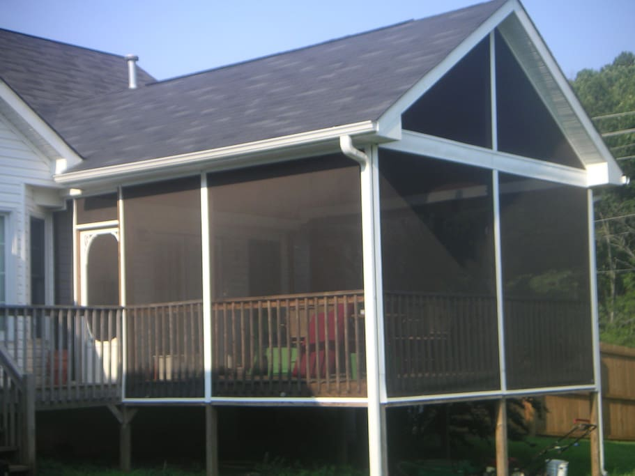An oversized screened in porch with a table for outdoor dining and a ping pong table you are welcome to enjoy!