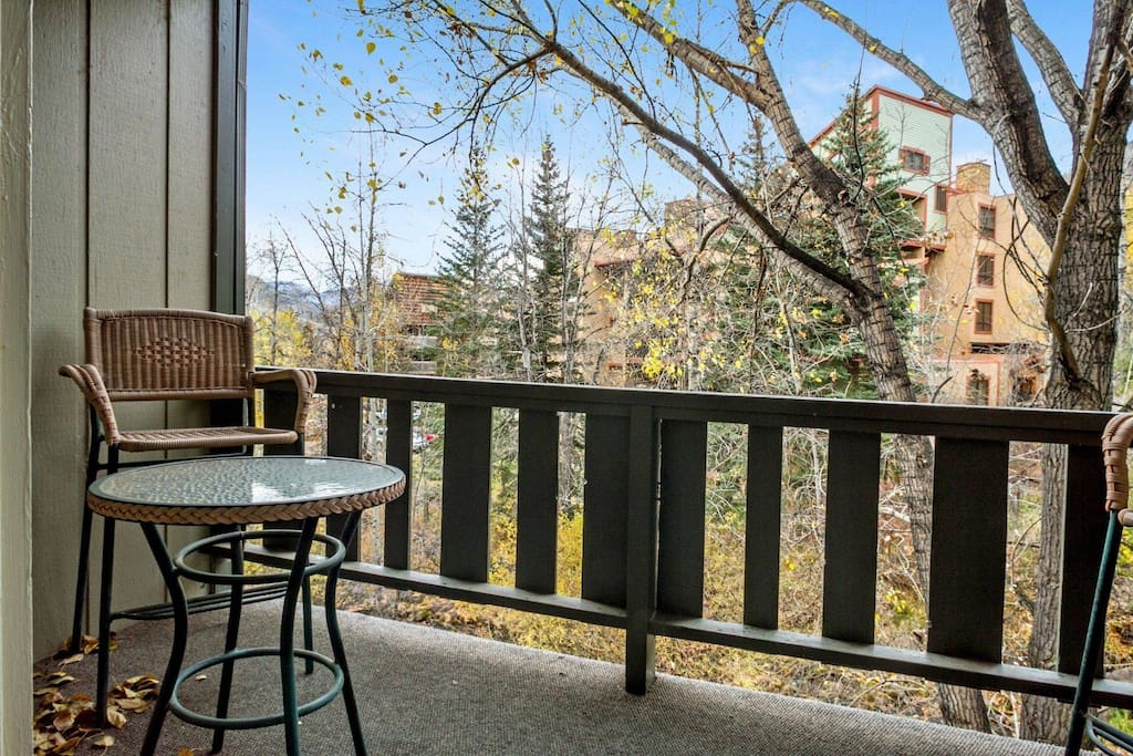 Deck with outdoor seating, overlooks the beautiful Gore Creek and open green space.