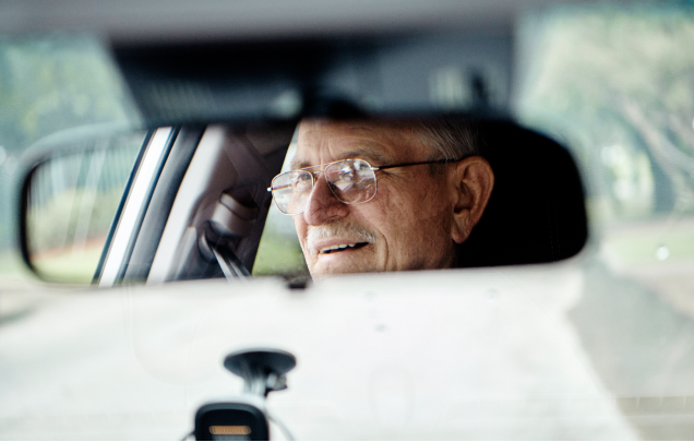 A rearview mirror in a car reveals the reflection of the driver, an older man wearing glasses.