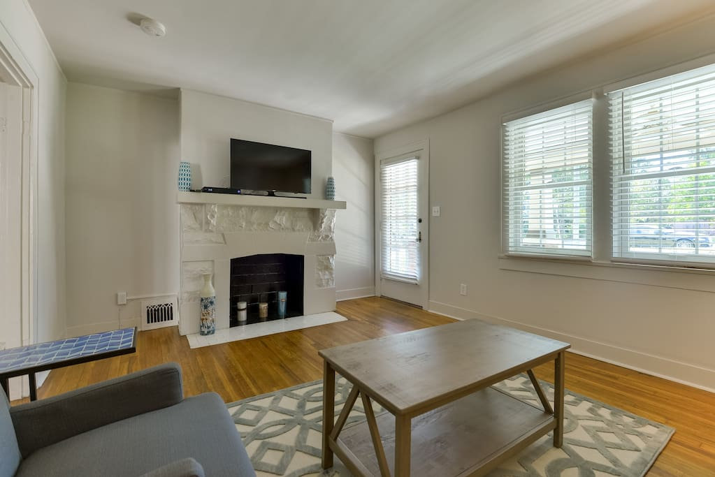 A lounge room is detailed with hardwood floors and offers an ornamental fireplace and flat-screen TV.