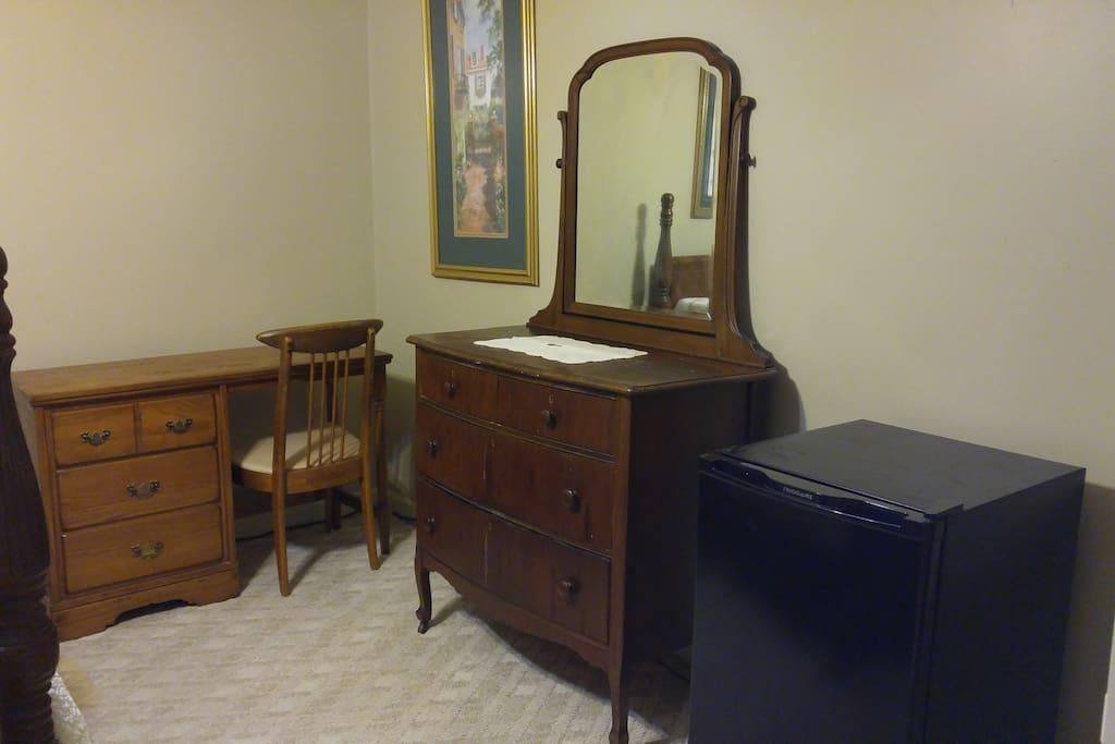 Dresser with mirror, desk and refrigerator.