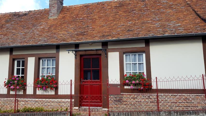 Petite maison normande dans village fleuri