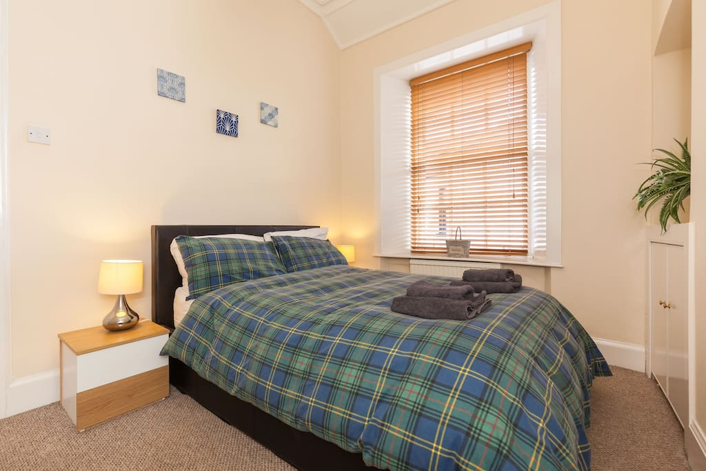 Comfortable double bed - full bedlinen and towels provided for all guests... wardrobe and drawers provides plenty of storage