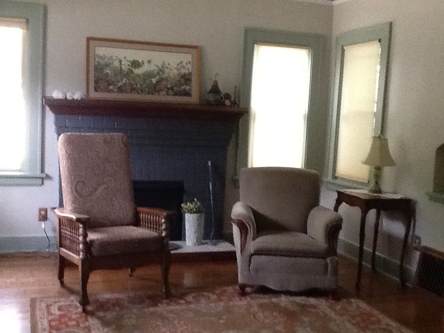 Living room with gas log fire place, big screen tv with Directv.  One couch and three chairs.
