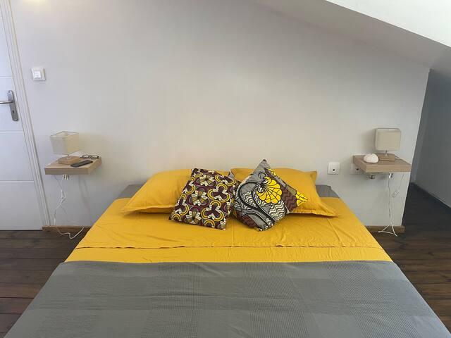 Chambre 1 côté mer lit queen size (160) équipée de la climatisation, d'un coin lavabo étagère et miroir et d'un espace étagères et penderie - accès direct à la douche et aux toilettes