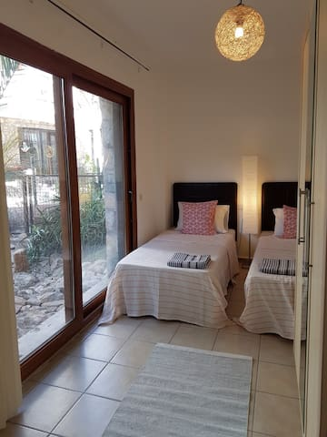 The twin bedroom with brand new mattresses & bedding with view to cactus garden with a beautiful palm tree