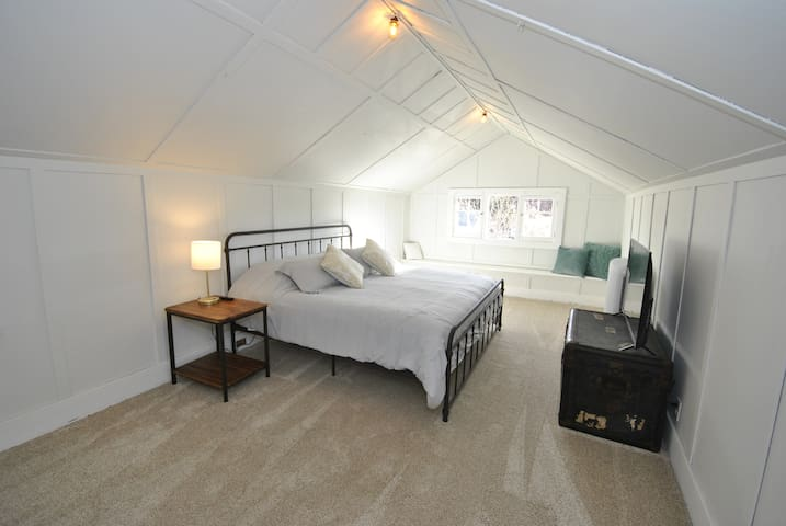 Upper bedroom with king sized bed and tv